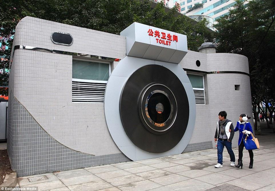 Chineses olham admirados para o banheiro público em forma de câmera fotográfica, em Shiqiaopu Street em Chonqging, China