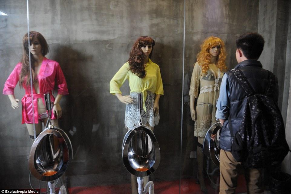 Um homem faz xixi em um banheiro em frente de três manequins femininos em traje provocante num restaurante em Taiyuan, província de Shanxi de China