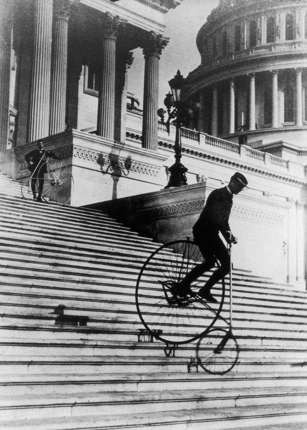 Homens montar penny-farthings descer os degraus do edifício do Capitólio dos Estados Unidos.