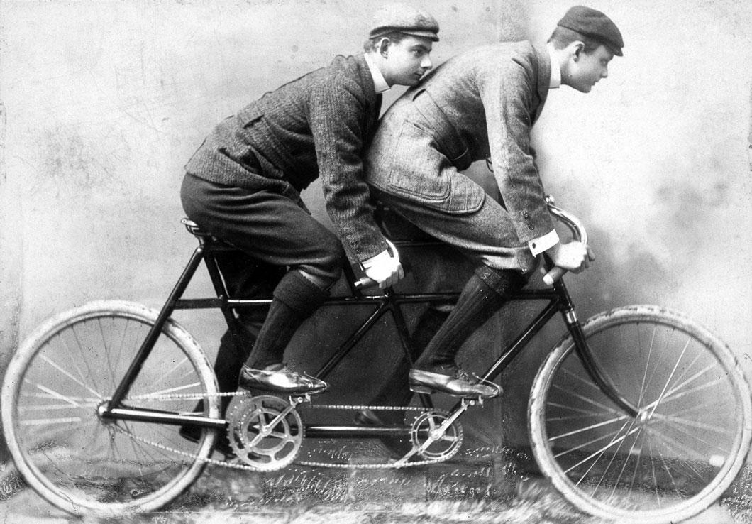 Charles Stewart Rolls (à direita), co-fundador da Rolls-Royce, monta uma bicicleta tandem com um estudante da Universidade de Cambridge companheiro.