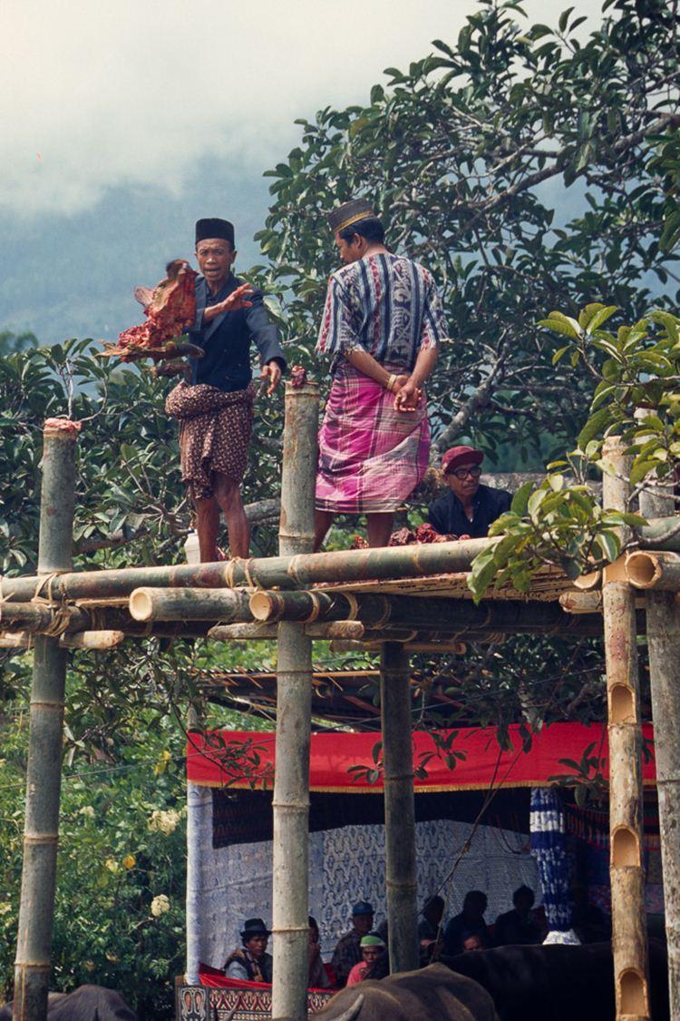 Numa plataforma, uma pessoa grita um nome e lhe joga um pedaço de carne e assim é feita a distribuíção da carne a toda a aldeia e aos convidados