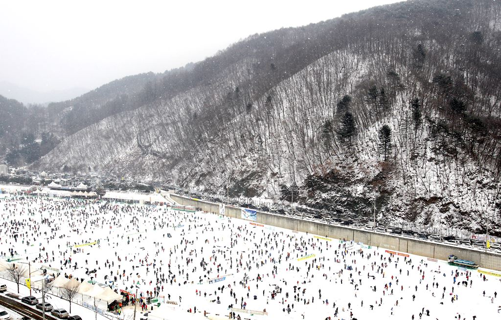 HWACHEON-GUN, SOUTH KOREA - JANUARY 05: Anglers cast lines through holes into a frozen river during an ice fishing competition at the Hwacheon Sancheoneo Ice Festival on January 5, 2013 in Hwacheon-gun, South Korea. The annual event attracts thousands of visitors and features a mountain trout ice fishing competition in which participants compete with tradition lures or with bare hands. (Photo by Chung Sung-Jun/Getty Images)